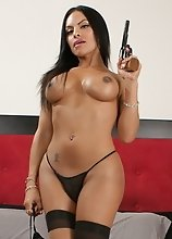 Gorgeous tgirl Foxxy posing naked with a gun